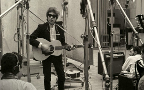 black-and-white photo of Bob Dylan wearing sunglasses and playing a guitar in a recording studio