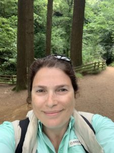 Woman posing for a selfie-photo in a forest while wearing a green top