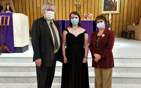 a man and two women wearing face masks and standing in front of a Christian altar