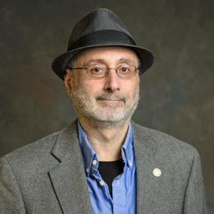 man with a grey beard, glasses, hat and blazer